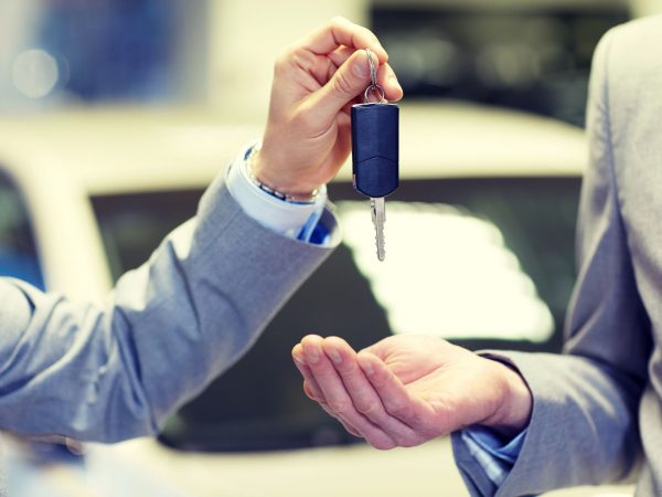 auto business, car sale, deal and people concept – close up of male hands with car key in auto show or salon